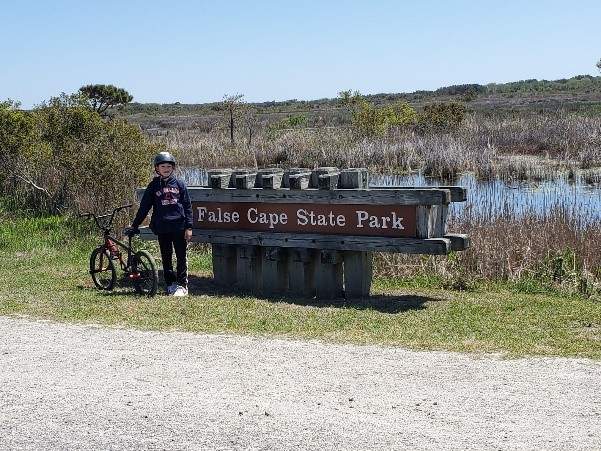 False Cape State Park sign and young bike rider