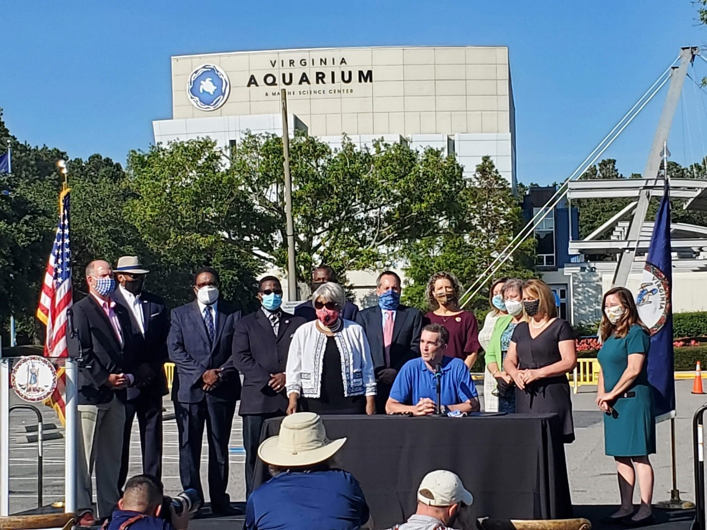 Governor Northam with state legislators from Hampton Roads at a table in front of the Virginia Aquarium signs offshore wind legislation.