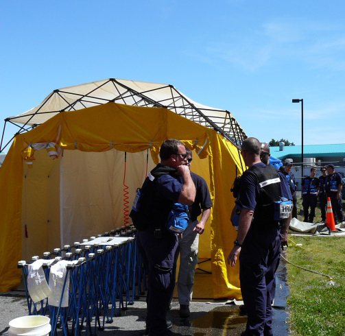 Depicts an Emergency Response Training Exercise, with a yellow decontamination tent and first responders planning response activities.