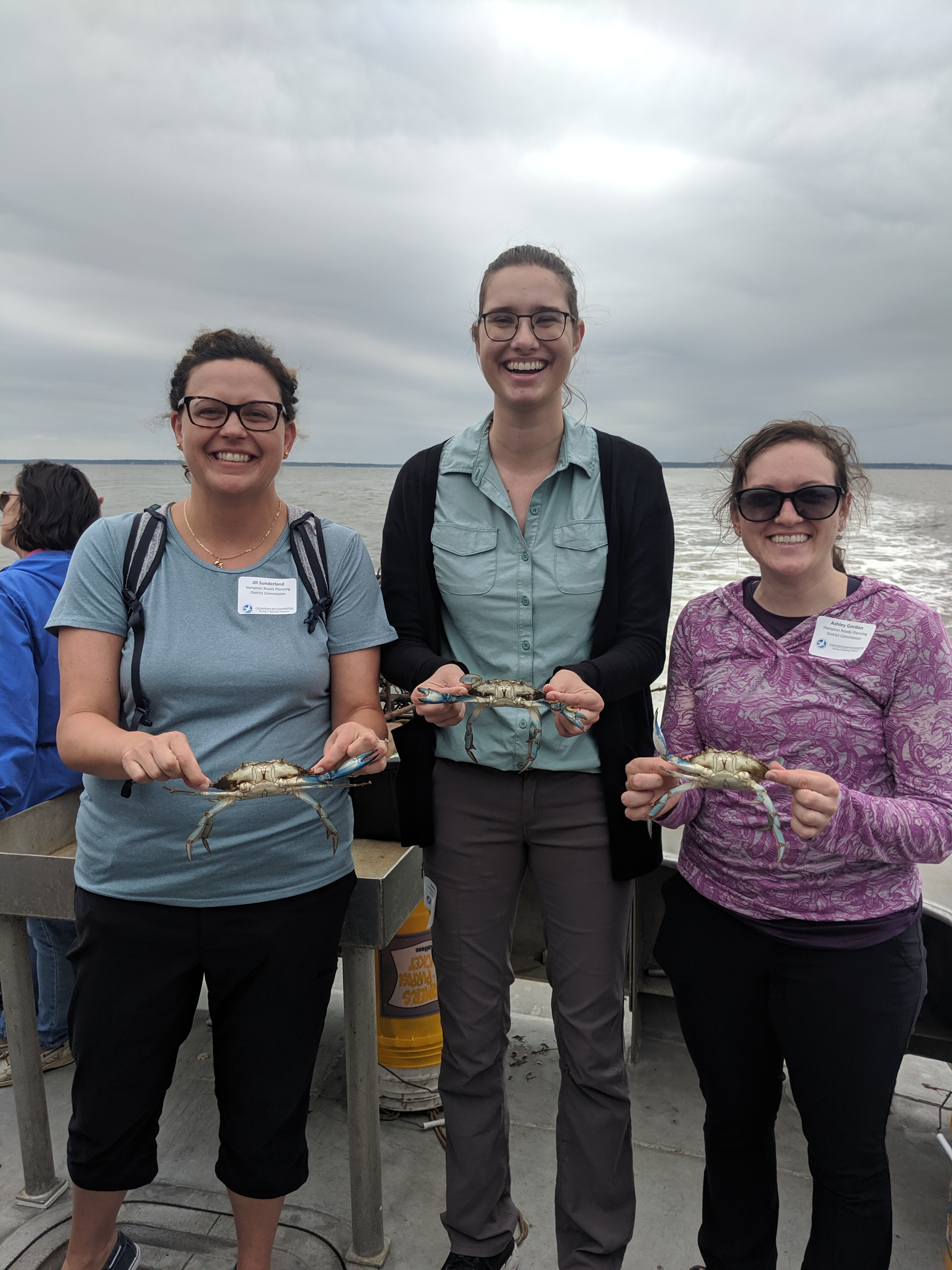 Ms. Jill Sunderland, Ms. Katie Krueger, and Ms. Ashley Gordon, are holding blue crabs.